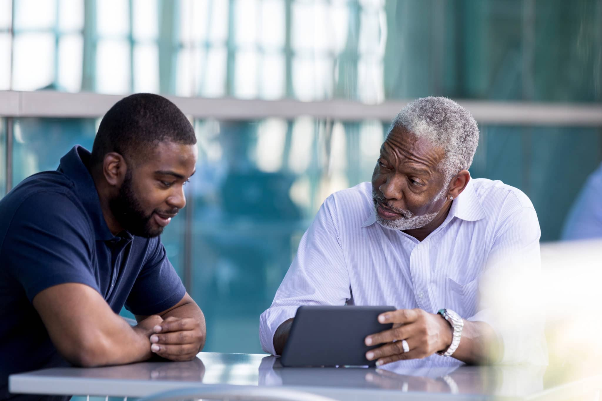 A senior African American businessman shows a male colleague something on a digital tablet while sitting outside on an office patio.